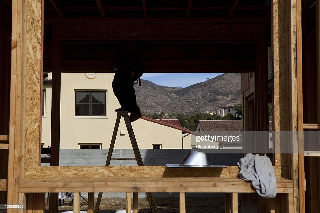 A worker stands on a ladder inside a house under construction at Davidson Communities LLC's Arista at The Crosby development in Rancho Santa Fe, California, U.S., on Friday, Dec. 21, 2012. New home sales climbed to a 380,000 annual rate in November, the most since April 2010, according to the median forecast of 60 economists surveyed by Bloomberg before Dec. 27 figures from the Commerce Department. Photographer: Sam Hodgson/Bloomberg via Getty Images