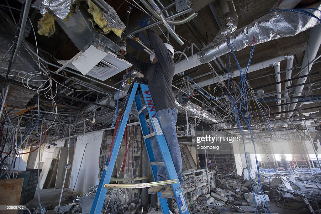 A worker stands on a ladder on the top floor at 75 Rockefeller Plaza during demolition ahead of renovations in New York, U.S., on Monday, Aug. 18, 2014. New landlord RXR Realty Corp. is upgrading the entire 630,000 square feet. The $150 million project includes raising office ceilings from 7.5 feet (2.3 meters) to 9 feet, and relocating mechanical equipment from the top floor to create new high-priced space, said Scott Rechler, RXRís chief executive officer. Photographer: Jin Lee/Bloomberg via Getty Images