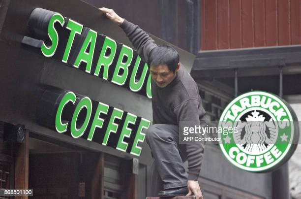 A worker stands on a ladder to fix a signboard of a Starbucks coffee shop in Chengdu China's southwestern province of Sichuan 18 January 2007 An...