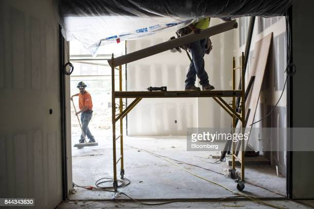 A worker stands on a platform to install a board inside the convention center of the Irvine Spectrum Marriott International Inc hotel a project of RD...