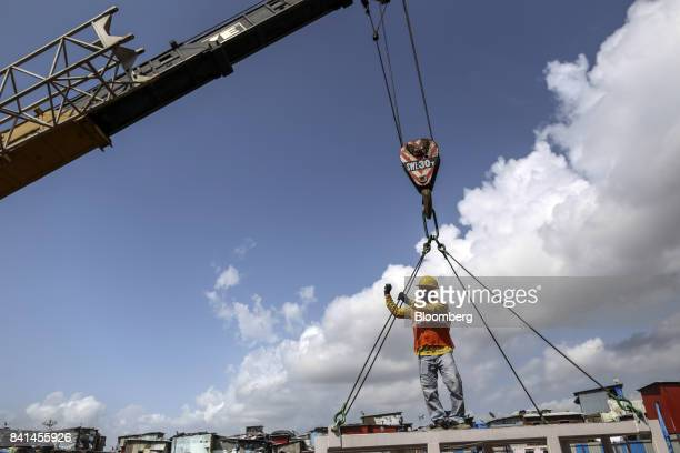 A worker stands on a rescue basket at the excavation site of a launching shaft for Metro Line 3 operated by the Mumbai Metro Rail Corp in the Dharavi...