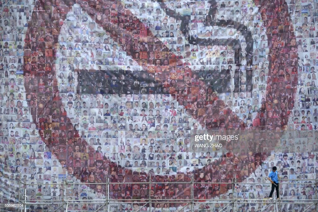A worker stands on a scaffold in front of a giant poster for World No Tobacco Day in Beijing on May 31, 2016. May 31 is observed as World No Tobacco Day, with the World Health Organisation (WHO) using 'Get Ready For Plain Packaging' as the slogan of this year's day. / AFP / WANG
