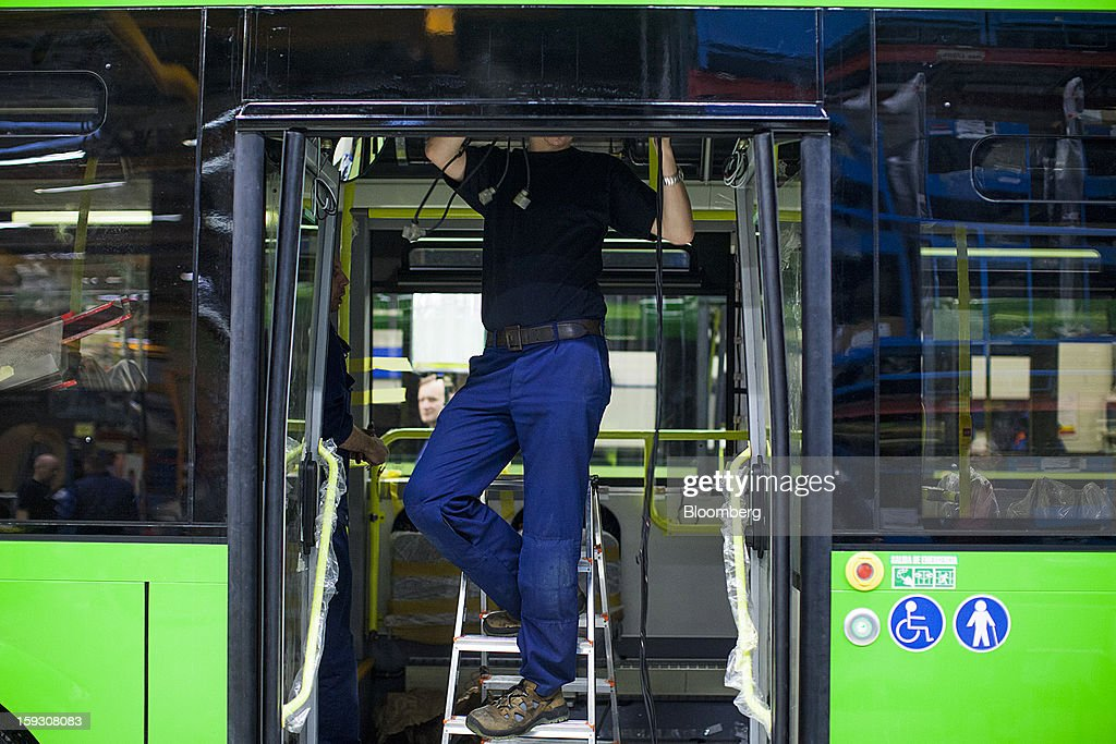 A worker stands on a stepladder to access the interior of a bus during assembly at Volvo AB's manufacturing plant in Wroclaw, Poland, on Friday, Jan. 11, 2013. Volvo plans to end bus making in Saeffle by June 2013, and will consolidate the business in Europe to its main plant in Wroclaw, Poland, the Gothenburg, Sweden-based company said. Photographer: Bartek Sadowski/Bloomberg via Getty Images