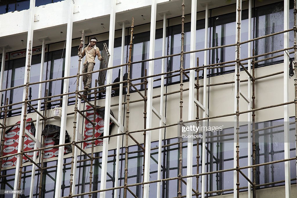 A worker stands on scaffolding in a construction site at a business park in Gurgaon, India, on Wednesday, March 26, 2014. Indian stocks rose, sending the benchmark index to a record, after the rupee rose to an eight-month high and sovereign bonds gained on speculation the worlds largest democracy will elect a government capable of reviving economic growth. Photographer: Kuni Takahashi/Bloomberg via Getty Images