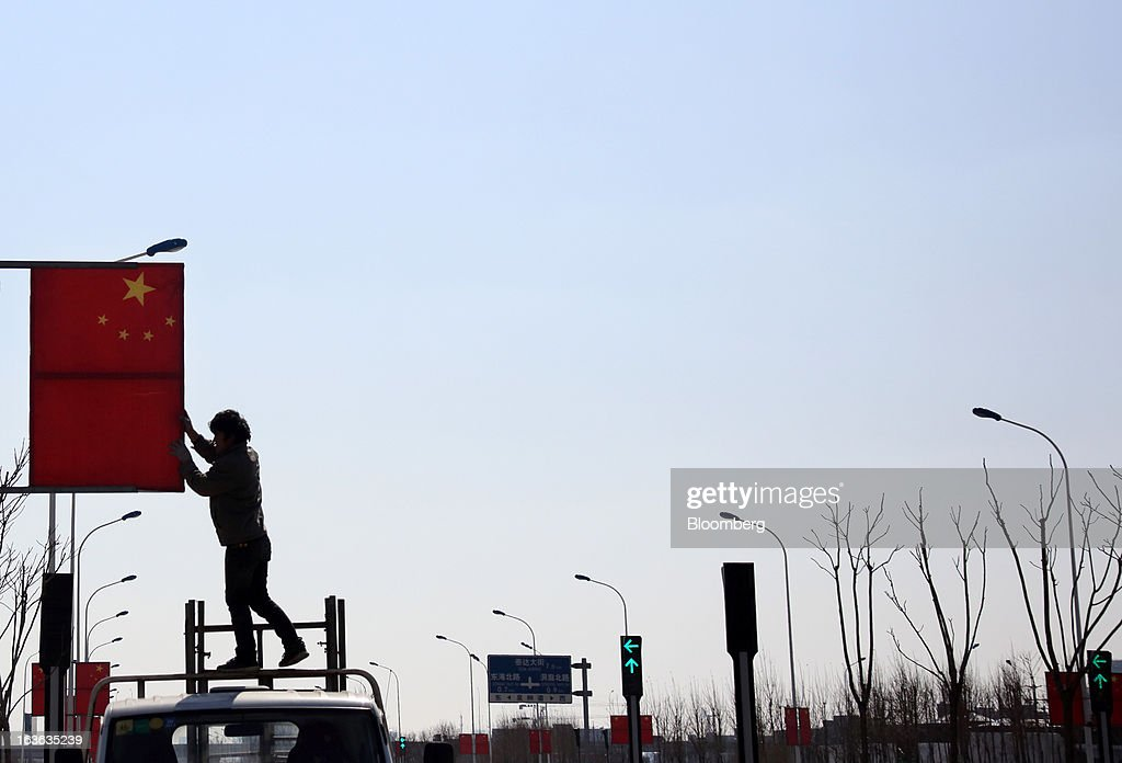 A worker stands on the roof of a truck as he installs Chinese flags on a lamp post on a street in Tianjin, China, on Wednesday, March 13, 2013. China's National People's Congress, or the legislature, will select the nation's president and vice president on March 14. Photographer: Tomohiro Ohsumi/Bloomberg via Getty Images