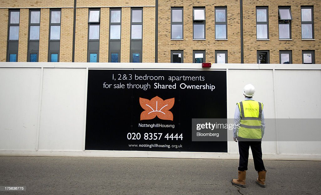 A worker stands outside the Oval Quarter, a shared ownership, private and social residential housing complex developed by Higgins Group Plc in partnership with Nottinghill Housing and Pinnacle Regeneration Group, in London, U.K., on Monday, Aug. 5, 2013. U.K. house prices rose 0.8 percent in July, from 0.3 percent the previous month, Nationwide Building Society said. Photographer: Simon Dawson/Bloomberg via Getty Images