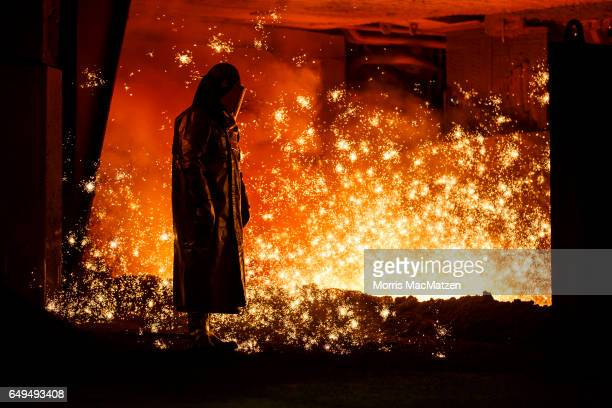 A worker stands over molten steel at the Salzgitter AG steelworks on March 7 2017 in Salzgitter Germany Salzgitter is among Europe's biggest steel...