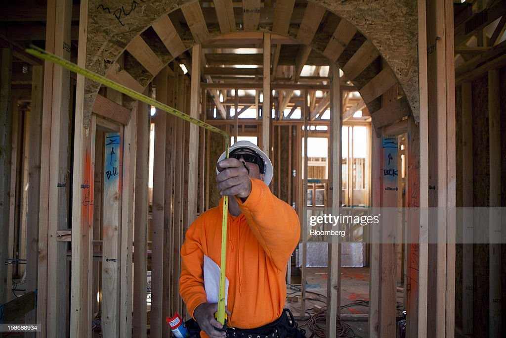 A worker stands under an archway as he takes measurements inside a house under construction at Davidson Communities LLC's Arista at The Crosby development in Rancho Santa Fe, California, U.S., on Friday, Dec. 21, 2012. New home sales climbed to a 380,000 annual rate in November, the most since April 2010, according to the median forecast of 60 economists surveyed by Bloomberg before Dec. 27 figures from the Commerce Department. Photographer: Sam Hodgson/Bloomberg via Getty Images