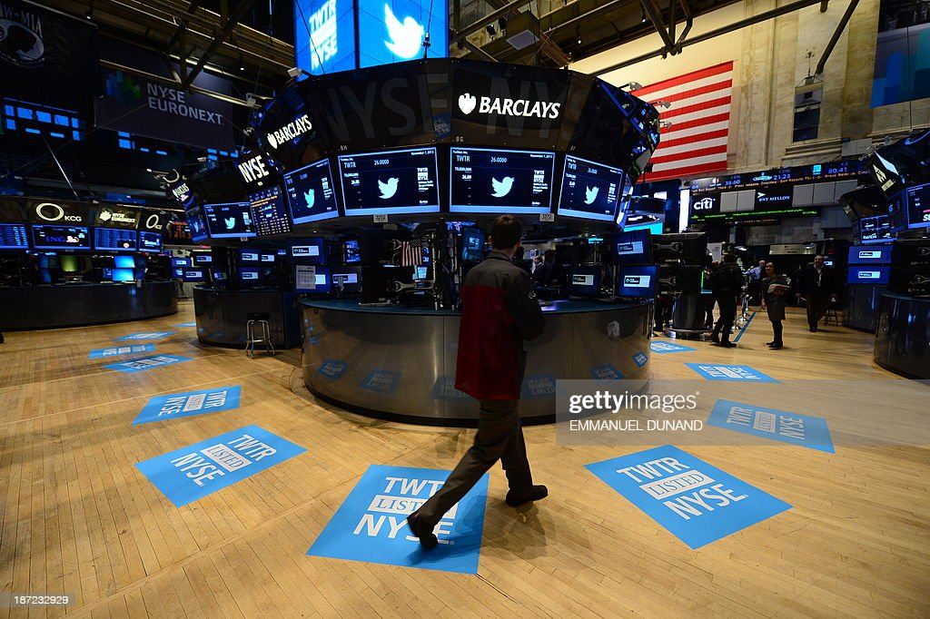 A worker stands walks near floor mats bearing the logo of Twitter and the symbol on which Twitter's stock will traded (TWTR) on the floor of the New York Stock Exchange (NYSE) on November 7, 2013 in New York. Twitter goes public on the NYSE today,and is expected to open at $26 per share, making the company worth an estimated 18 billion USD . AFP PHOTO/EMMANUEL DUNAND