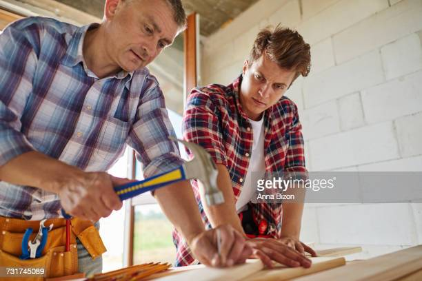 Worker sticking nail into wooden plank. Debica, Poland