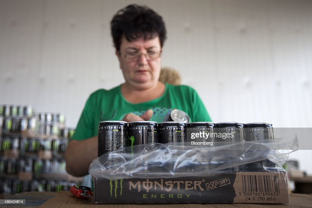 A worker sticks Greek language labels onto Monster Energy drinks cans ahead of distribution at the Lanitis Bros Ltd. bottling plant, part of the Coca-Cola Hellenic Group, in Nicosia, Cyprus, on Tuesday, June 10, 2014. Zug, Switzerland-based Coca-Cola Hellenic Bottling Co., which distributes Coca-Cola products in countries including Russia, wants to move away from using imported sugar for its Russian operations by 2015. Photographer: Andrew Caballero-Reynolds/Bloomberg via Getty Images