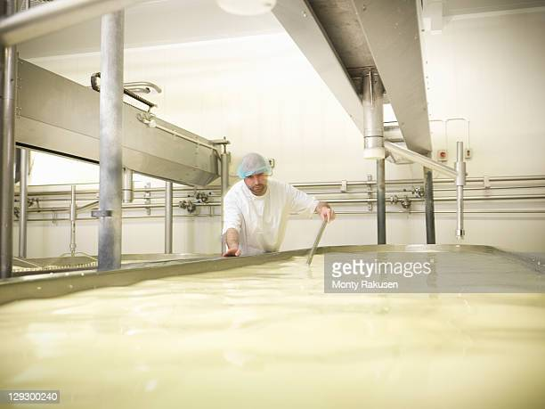 Worker stirring milk for cheese-making