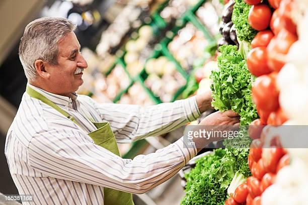 Worker Stocking Produce On Vegetable Shelf