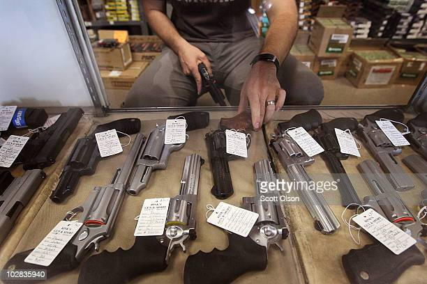 A worker stocks pistols being offered for sale at Rinks Gun and Sport in suburban Chicago on July 12 2010 in Lockport Illinois Chicago began...