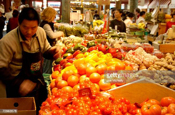 A worker stocks vegetables at one of the many openair produce markets on tiny Granville Island April 18 2004 in Vancouver Canada Though Canada's...