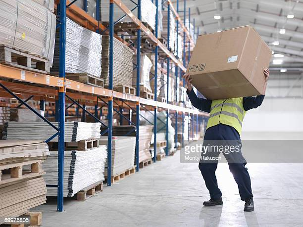Worker Struggling With Box In Warehouse