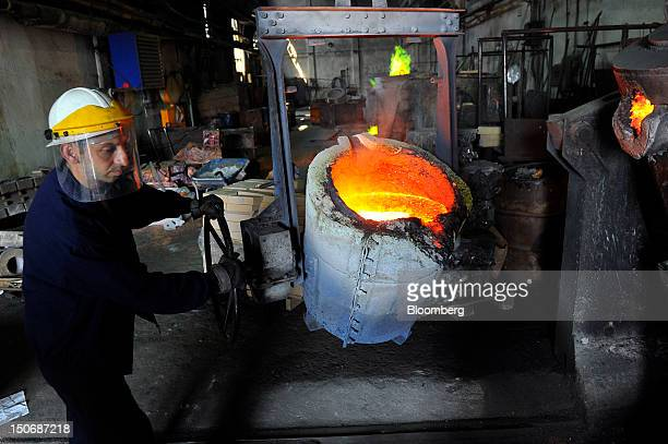 A worker supervises the movement of molten brass a mixture of copper and zinc using a cauldron in the foundry at the copper mining and smelting...