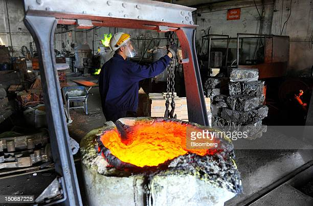A worker supervises the movement of molten brass a mixture of copper and zinc in a cauldron before pouring into moulds in the foundry at the copper...