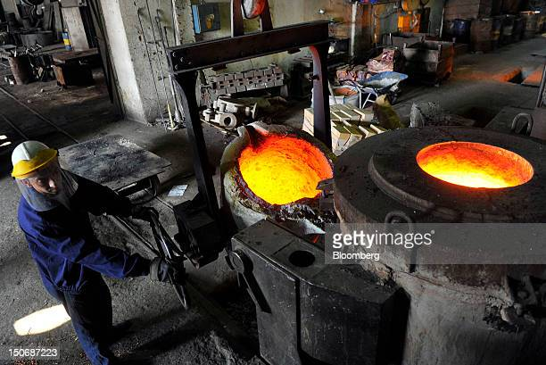 A worker supervises the pouring of molten brass a mixture of copper and zinc from a furnace into a cauldron in the foundry at the copper mining and...