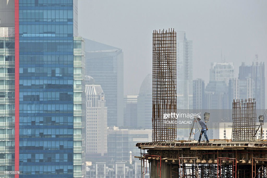A worker surveys a high rise office building under construction in Jakarta on May 14, 2013. Indonesia held its key interest rate at 5.75 percent on May 14, 2013 for the 15th consecutive month after the economy expanded at the slowest pace for more than two years in the first quarter.