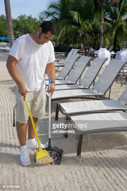 A worker sweeping the beach outside Key Largo Resort at Manatee Bay
