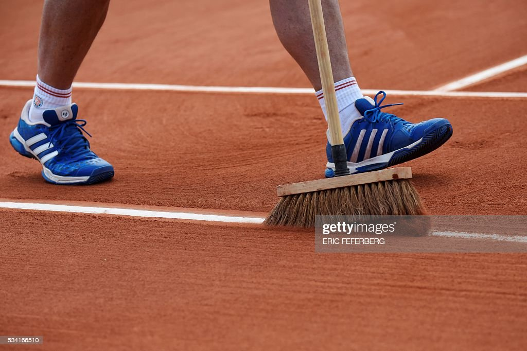 A worker sweeps a line on the court during a match at the Roland Garros 2016 French Tennis Open in Paris on May 25, 2016. / AFP / Eric FEFERBERG