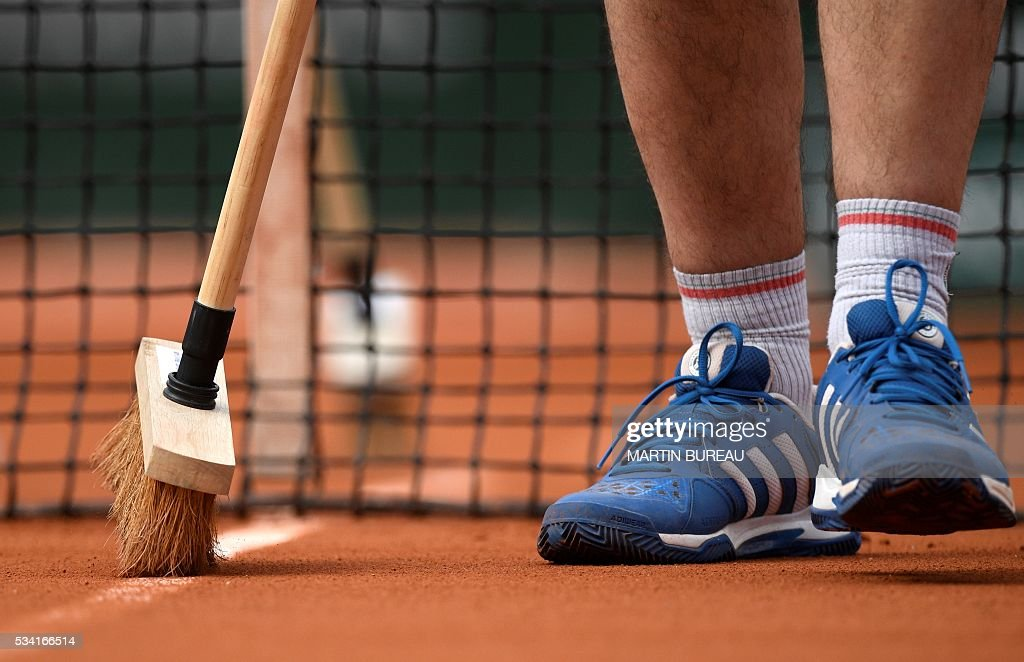 A worker sweeps a line on the court during a match at the Roland Garros 2016 French Tennis Open in Paris on May 25, 2016. / AFP / MARTIN