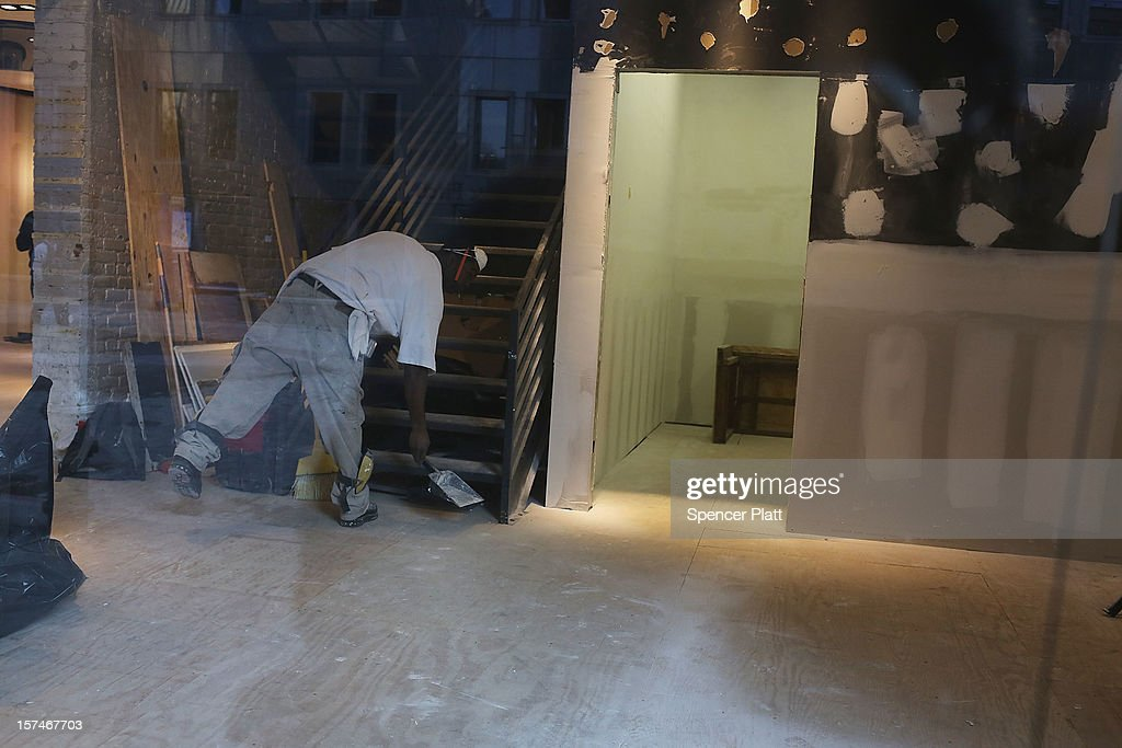 A worker sweeps at flood damaged business affected by Superstorm Sandy in South Street Seaport on December 3, 2012 in New York City. South Street Seaport, an area popular with tourists which was about to go through a major redevelopment, suffered severe damage from Hurricane Sandy. Most of the buildings and businesses, including the South Street Seaport Museum, suffered severe flooding and remained closed. According to a new Siena Research Institute poll, most New Yorkers overwhelmingly agree that climate change was behind Hurricane Sandy.