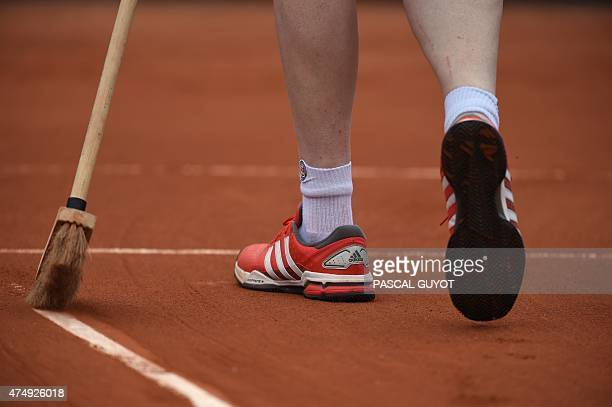 A worker sweeps the clay from the line on a tennis court at the Roland Garros 2015 French Tennis Open in Paris on May 28 2015 AFP PHOTO / PASCAL GUYOT