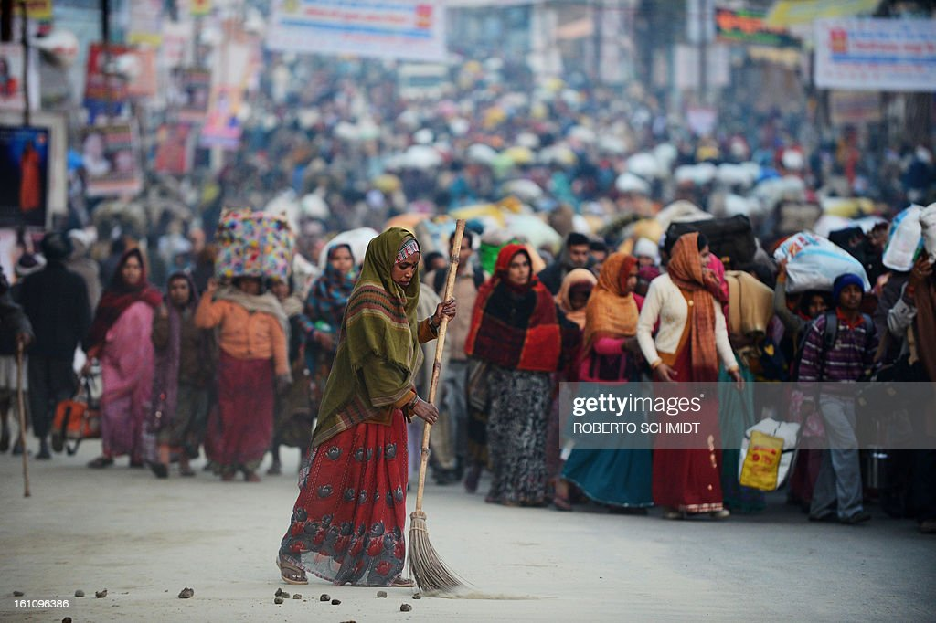A worker sweeps the street at one of the crowd entrance points to the grounds where the Kumbh Mela is taking place in Allahabad on February 9, 2013. The Kumbh Mela in the town of Allahabad will see up to 100 million worshippers gather over 55 days to take a ritual bath in the holy waters, believed to cleanse sins and bestow blessings.