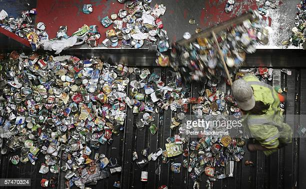 A worker sweeps up tin cans at the Materials Recovery Facility on April 27 2006 in Leatherhead England The GBP5 million plant has an annual capacity...