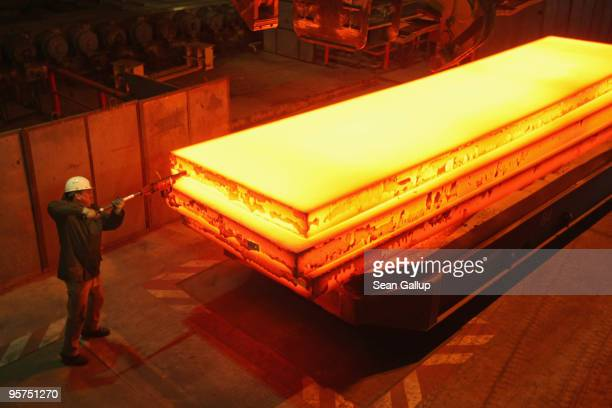 A worker tags a giant block of heated steel at the rolling mill at the ThyssenKrupp steelworks on January 13 2010 in Duisburg Germany Recent economic...