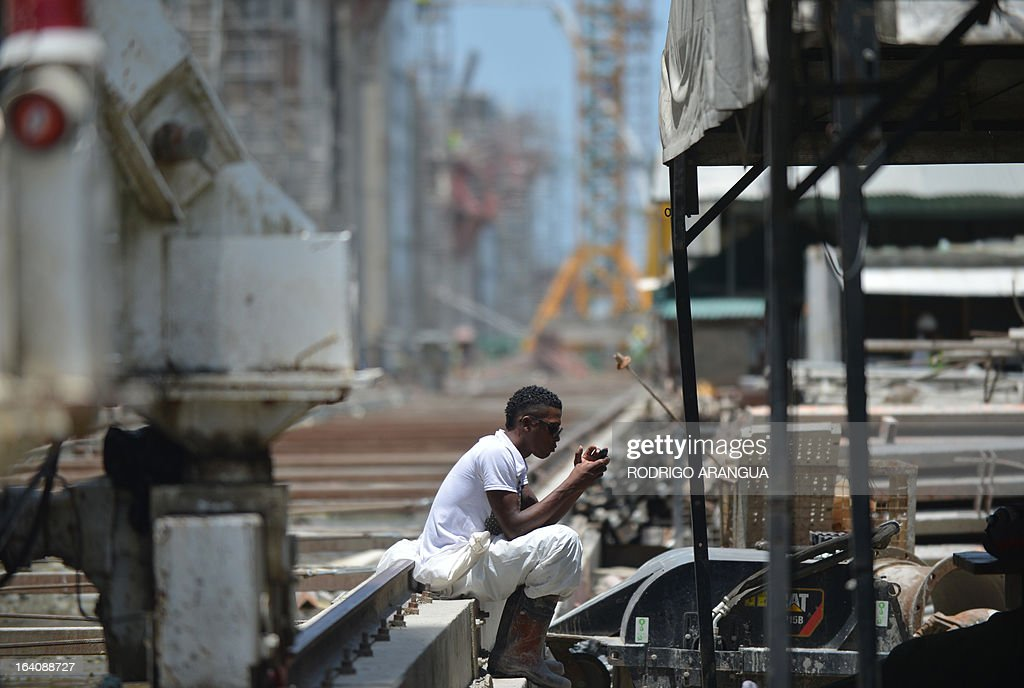 A worker takes a break at the site of the new Panama canal locks being constructed, led by Spanish company Sacyr, in Puerto Colon, Panama, next to the Atlantic Ocean on March 19, 2013. The new locks will allow the passage of freighters with a cargo capacity of up to 12,000 containers. AFP PHOTO/ Rodrigo ARANGUA