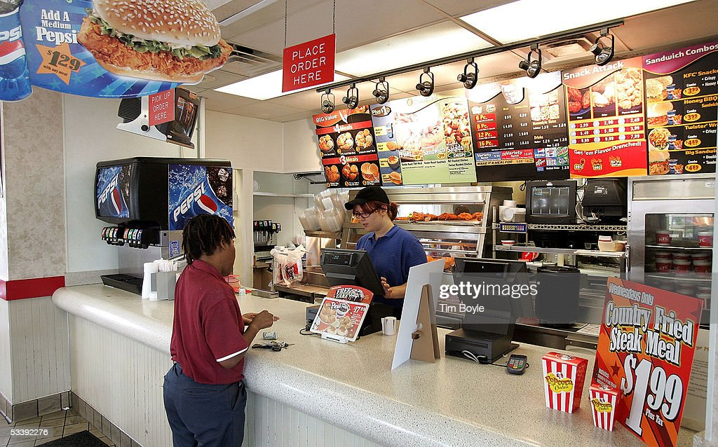 A worker takes a customer's order in a cigarettesmokefree KFC restaurant August 15 2005 in Chicago Illinois Louisville Kentuckybased Yum Brands'...