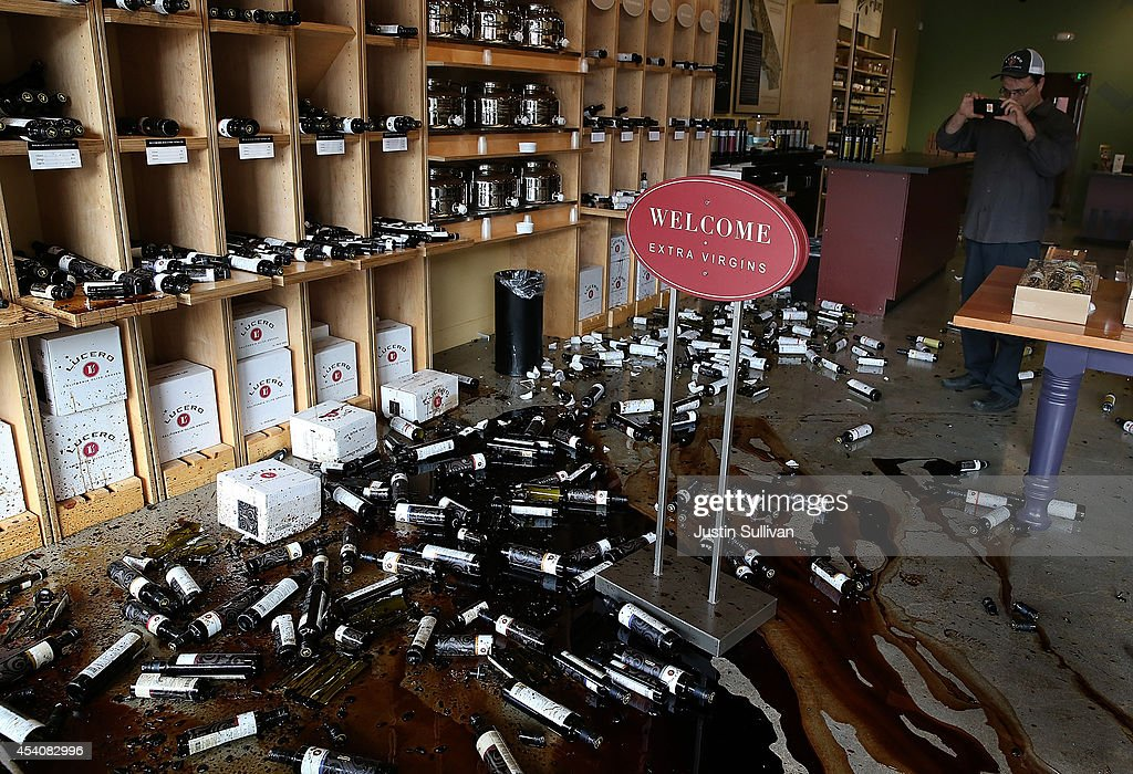 A worker takes a picture of bottles of olive oil and vinegar that were thrown from the shelves of an olive oil store following a reported 6.0 earthquake on August 24, 2014 in Napa, California. A 6.0 earthquake rocked the San Francisco Bay Area shortly after 3:00 am on Sunday morning causing damage to buildings and sending at least 70 people to a hospital with non-life threatening injuries.