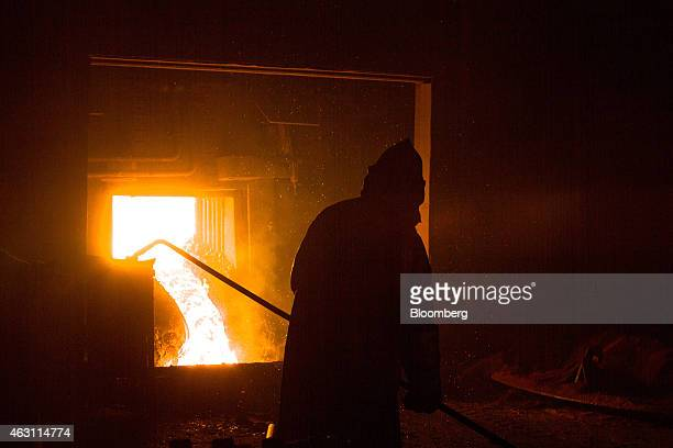 A worker takes a sample of molten steel from an arc furnace in operation at the metallurgical mill operated by OAO Novolipetsk Steel also known as...
