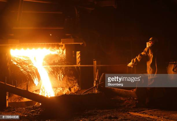 A worker takes a sample of molten steel from an arc furnace in the smelting shop at the Oskol Elektrometallurgical Plant steel mill operated by...