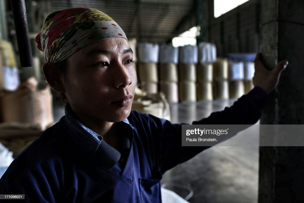 A worker takes break from filling bags of rice at the Settapanich -Samchuk rice mill in on June 20, 2013 in Suphan Buri, Thailand. Thailand plans to sell as much as 7 million metric tons from inventories in order to fund a grain purchase program. Recently financial sources revealed that the actual losses from the government's controversial rice pledging scheme for the 2011-12 rice harvest year are close to reaching 200 billion baht [US$6.5 billion], this is far above the Thai Finance Ministry's earlier forecast of 70-100 billion baht.