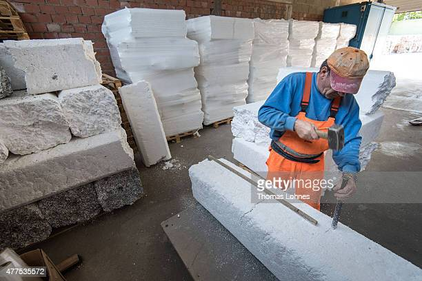 A worker takes compressed blocks with white styrofoam of packaging to conveyor at the 'DRZ Darmstaedter Recycling Zentrum GmbH' on June 17 2015 in...