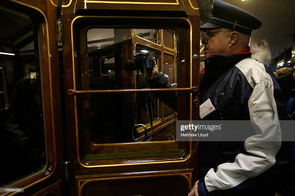 A TFL worker takes pictures inside the first class carriages pulled by a restored steam engine built in 1898, known as Met Locomotive No. 1, after it arrives at Moorgate station in a recreation of the first London Underground journey on January 13, 2013 in London, England. The London Underground celebrates its 150th birthday this month, the Metropolitan line being the first stretch between Paddington and Farringdon stations.