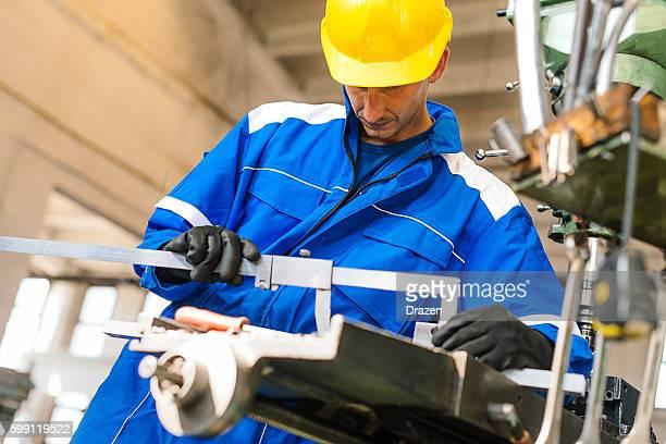 Worker taking measures of metal part