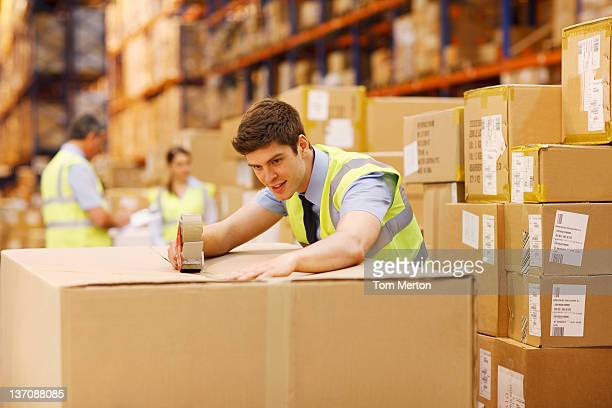Worker taping box in warehouse