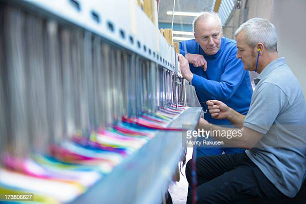 Worker teaching apprentice to use industrial loom in textile mill