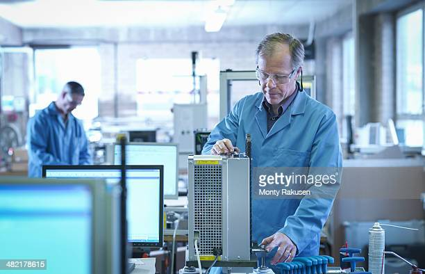 Worker testing equipment on production line