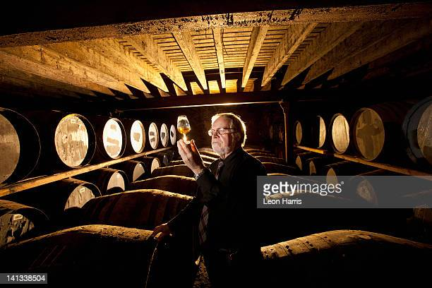 Worker testing whisky in distillery