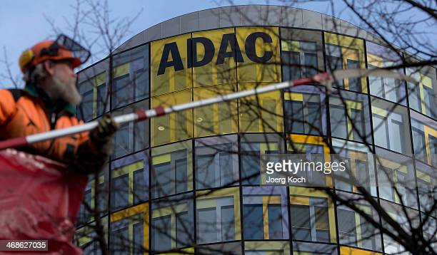 A worker thins out a tree in front of the headquarter and logo of the German Automobile Association Club ADAC on February 11 2014 in Munich Germany