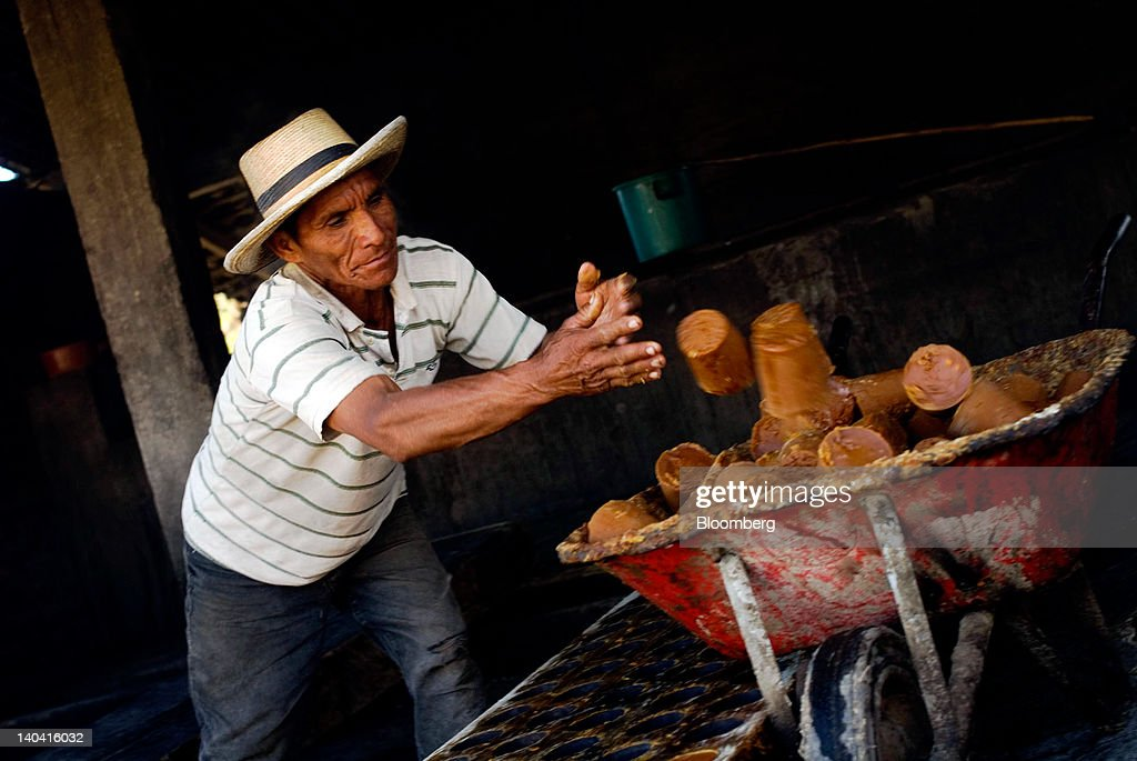 A worker thows blocks of handmade panela, a solid piece of unrefined whole cane sugar obtained from the boiling and evaporation of sugarcane juice, into a barrel at a traditional sugar mill in Tepetitan, El Salvador on Sunday, Feb. 26, 2012. Global sugar supply will be 'under pressure' amid significant demand growth by 2020, which may push prices up further, according to Mannheim, Germany-based refiner Suedzucker AG. Photographer: Juan Carlos/Bloomberg via Getty Images