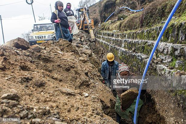 A worker throws a rock at a road construction site near the Nathula Pass an open trading post in the Himalayas between India and China in Sikkim...