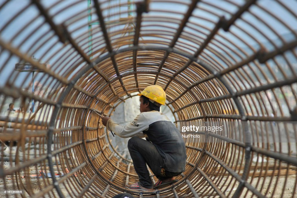 A Worker tighten Iron pillar for welding on-going Bridge expansion work supported by China AID at Kalanki, Kathmandu, Nepal on Monday, July 17, 2017. The workers used to earn daily wage of NRs. 800 (US$ 8) per day.