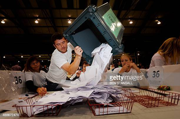 A worker tips out a ballot box in the Aberdeen Exhibition and Conference Centre in Aberdeen on September 18 immediately after the polls close in the...